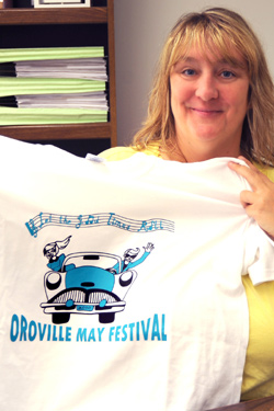 Michelle Smith, President of the May Festival Committee holds up this year's festival T-shirt, with the