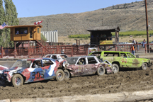 Brandon Weller in the #44 car, the lime green Rough and Tough station wagon, helps to sandwich another car during the Tonasket Demolition Derby presented by the Commancheros Rodeo Club. Weller won three heats and the overall prize as the last car still ru
