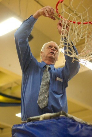Oroville girls basketball coach Mike Bourn cuts down the net after the Hornets wrapped up the Central Washington  2B League North Division title with a 44-34 victory over Lake Roosevelt on Tuesday, Feb. 11.